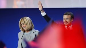 Brigitte Trogneux ja Emmanuel Macron seisovat esiintymislavalla. Macron heiluttaa kättään. Etualalla joku heiluttaa jonkinlaista punaista vaatetta, joka näkyy kuvassa punaisen värin leiskahduksena.