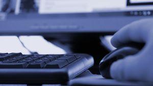 Kuvassa tietokoneen näppäimistö, hiiri ja miehen käsi
