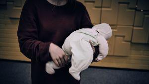 Äiti ravistaa vauvaa.
