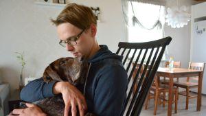 Tomi Vesterinen istuu kiikkutuolissa Bono-koira sylissään.