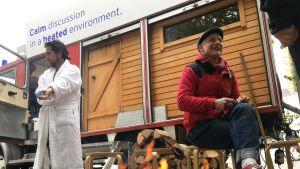 Taiteilija Dida Zende (oik.) lämmittää paloautoon rakentamaansa saunaa Euroopan parlamentin edustalla.