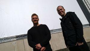 Antti Juntunen ja Henry Erkkilä virittävät valkokankaan teollisuushallin seinään.