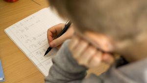 Lapsi laskee matematiikan tehtäviä.