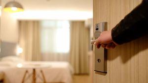 käsi hotellihuoneen ovenkahvalla