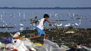 poika juoksee rannalla jossa paljon muoviroskaa