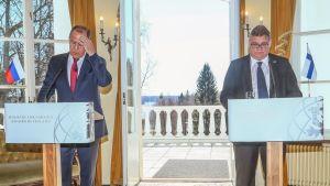 Lavrov ja Soini seisovat harmaissa puvuissa salissa puhujanpönttöjen takana avoimen parvekkeen oven edessä.