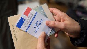 Äänestäjä piteli äänestyslipuketta kädessään Tullessa, Keski-Ranskassa sunnuntaina