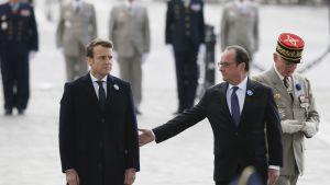 Hollande ojentaa kättä varautuneelle Macronille, taustalla univormupukuisia veteraaneja.