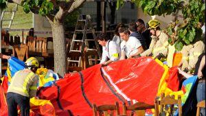 Iso punainen muovikangas, palomiehiä ympärillä.
