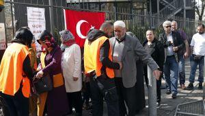 Ihmisiä seisoo jonossa. Oranssiliivinen mies tarkastaa vanhempaa miestä, oranssliliivinen nainen puolestaa huivipäisen naisen laukkua.