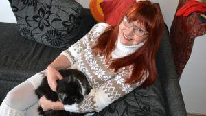 Punatukkainen, silmälasipäinen Saimi Anias kissa sylissään sohvalla.