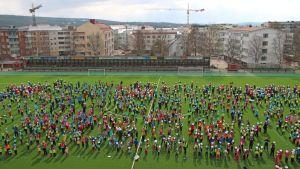 1250 lasta yrittävät muodostaa Rovaniemen keskuskentälle Suomen lipun pitämällä päänsä päällä sinisiä ja valkoisia papereita.