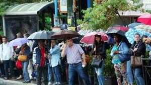 Ihmiset odottavat bussipysäkillä 17. toukokuuta Ateenassa.