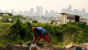 Mies kaataa vettä ämpäristä kaatopaikan liepeillä.