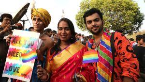 Intialaisiin värikkäisiin asuihin pukeutuneita miehiä ja nainen paraatissa