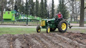 Maanviljelijä ajaa traktorilla perunapellon laidalla