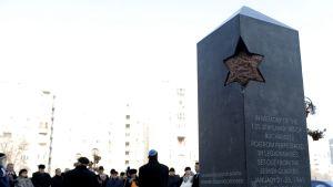 Muistomerkki, taustalla ihmisiä.