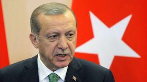 Erdogan puhuu, taustalla näkyy Turkin lippu.
