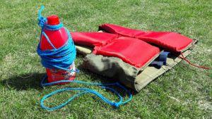 Mehukatti-pullo ja pelastusliivit ruohikolla