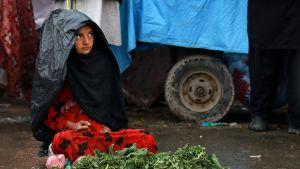 Sadeviittaan kietoutunut tyttö istuu kadulla edessään vihanneksia.