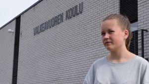 nuori tyttö seisoo ulkona koulurakennuksen vieressä