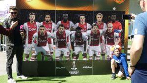 Ihmiset ottavat kuvia Ajaxin pelaajia esittävän kuvan edessä.