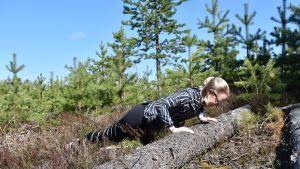 Teija Kuronen punnertaa kaatunutta runkoa vasten.