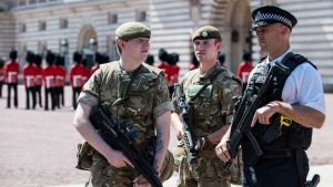 Kaksi aseistettua sotilasta ja aseistettu poliisi, taustalla puna-asuiset vartijat.