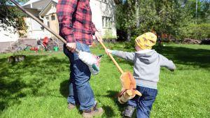Isä ja lapsi leikkivät keppihevosilla ulkona.