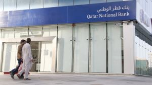 Kaksi miestä kävelee Qatarin pankkirakennuksen ohi.