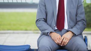 mies istuu bussipysäkillä