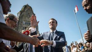 Emmanuel Macron kättelee ihmisiä poistuessaan äänestyspaikaltaan Le Touquetissa.