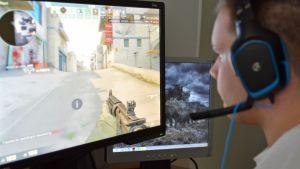 Mies pelaa tietokoneella.
