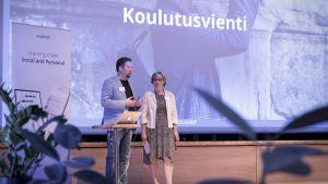 Kaksi ihmistä seisoo lavalla.