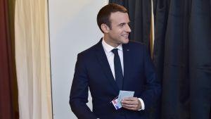 Macron äänestyskopin edessä äänestyslippu kädessä.