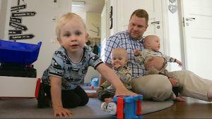 Monikkoperheen isä Marko Oikarainen 3-vuotiaan esikoisen Ollin ja 1-vuotiaiden kaksospoikien Aleksin ja Topiaksen kanssa.