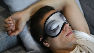 Mies nukkuu unimaski kasvoillaan.