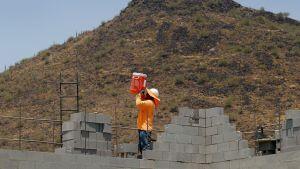 Mies juo vettä äärimmäisessä helteessä rakennustyömaalla Phoenixissa, Arizonassa.