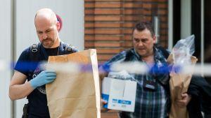 Poliisit kantavat tavaraa asunnosta paperipusseissa ja laatikossa.