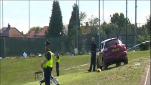 Kuvassa kolme poliisia seisoo punaisen henkilöauton lähellä. Alue on eristetty nauhalla.