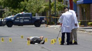 Tutkijat tekevät murhan rekonstruointia Meksikon kadulla.