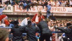 Poliisit yrittävät auttaa Liverpoolin kannattajaa Hillsborough'n stadionilla 1989.