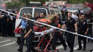 Lääkintähenkilöstö poistumassa sairaalasta New Yorkissa, jossa kuoli ainakin yksi ihminen ampumavälikohtauksessa.