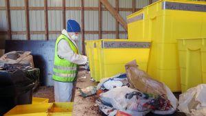 Nainen tutkii jätteitä.