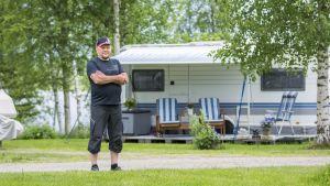 Mies seisoo leirintäalueella asuntovaunun edessä.