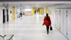Nainen kävelee sairaalan käytävällä.
