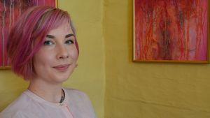Nainen seisoo kahden fuksianpunaisen maalauksen edessä.