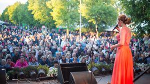 nainen laulaa yleisön edessä