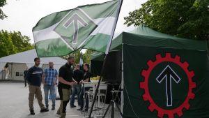 Pohjoismainen vastarintaliikkeen edustajat seisoskelevat teltallaan odottamassa kiinnostuneita.