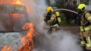 Palomiehet sammuttavat palavaa postin jakeluautoa.